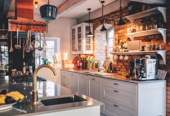 Kök i restaurangstil med tegelvägg och öppna hyllor