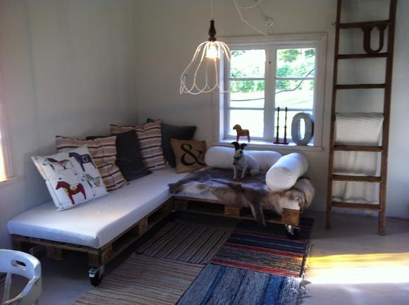 soffa av pallar,nakenlampa,stege,trasmattor,renskinn