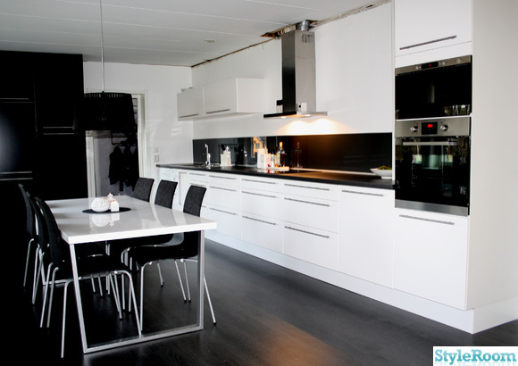 kök,köksbord,svart lampa,svarta stolar,svarta skåpluckor