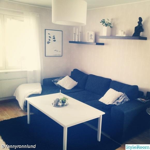 vardagsrum,mörkgrå soffa,vitt soffbord,ljusstakar silver,vit ram