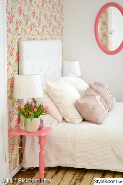 Färgglatt sovrum med rosa sängbord och blommig tapet