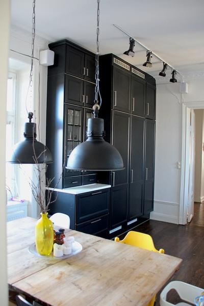 Svarta höga köksskåp i sekelskifteslägenhet